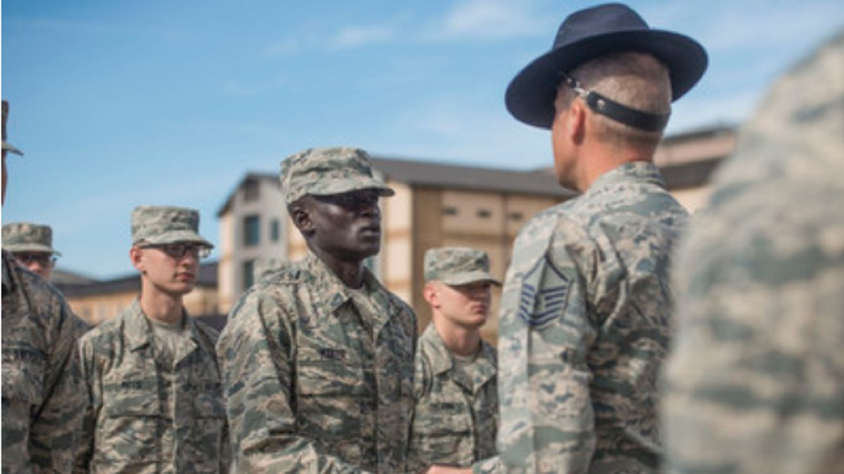 """Gour Maker, a trainee at basic military training, receives an """"Airman's Coin"""" at the Coin Ceremony Feb. 1, 2018 outside the Pfingston Reception Center at Joint Base San Antonio-Lackland, Texas. Maker was recognized by his wingmen as a selfless leader and motivator during his time at BMT. (Photo by Airman 1st Class Dillon Parker)"""