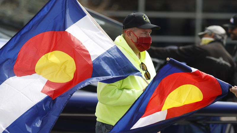 Wearing a face mask, Scott McMillan hands out flags of Colorado to some of the dozens of local...