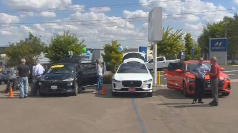 People check out electric cars at the event.