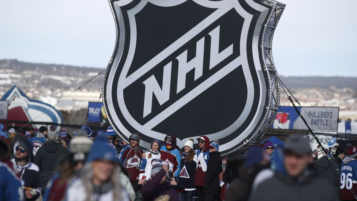 FILE - In this Feb. 15, 2020, file photo, fans pose below the NHL league logo at a display...