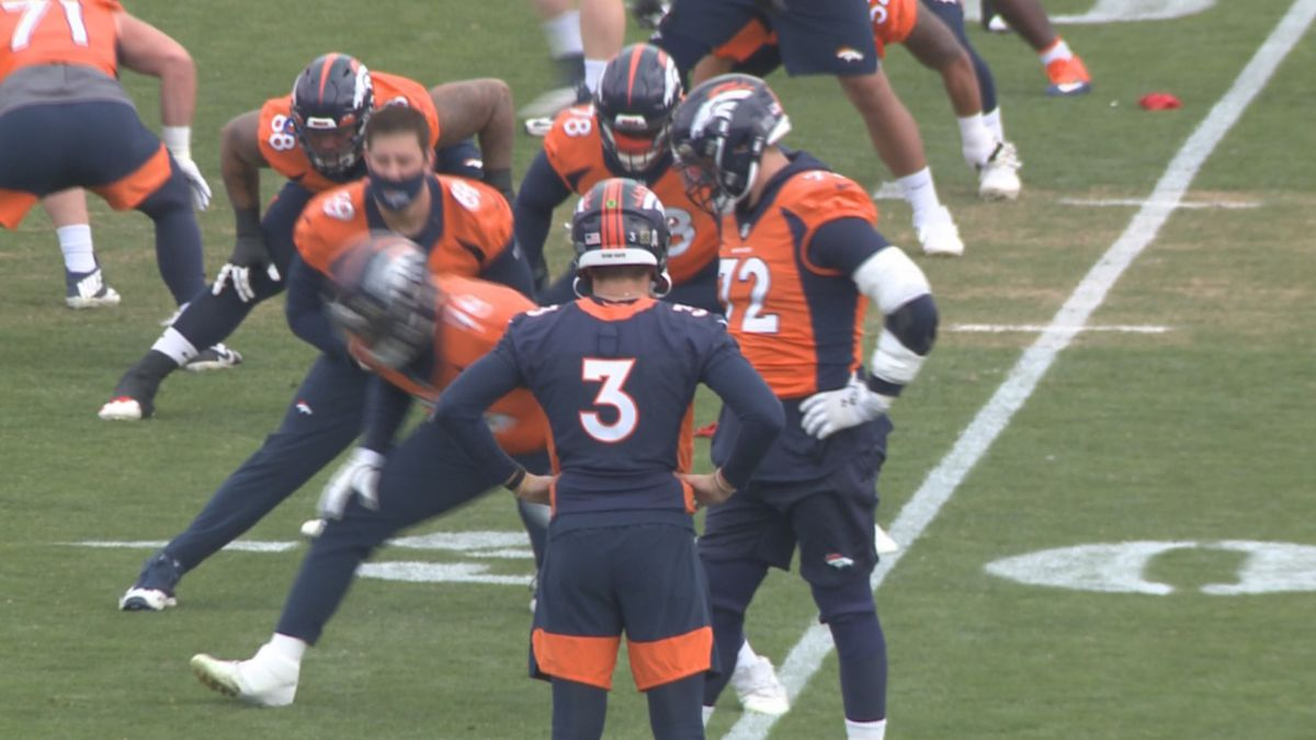 Drew Lock stands on the sidelines but did not participate at Broncos practice Wednesday at UC...