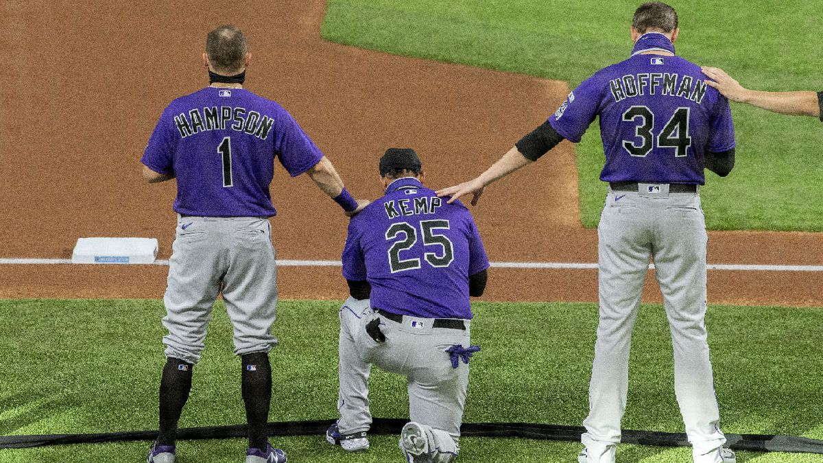 Colorado Rockies' Garrett Hampson (1) and Jeff Hoffman (34) place their hands on Matt Kemp (25) as he takes a knee during a moment of silence in recognition of the Black Lives Matter movement before an opening day baseball game against the Texas Rangers, Friday, July 24, 2020, in Arlington, Texas. (AP Photo/Jeffrey McWhorter)