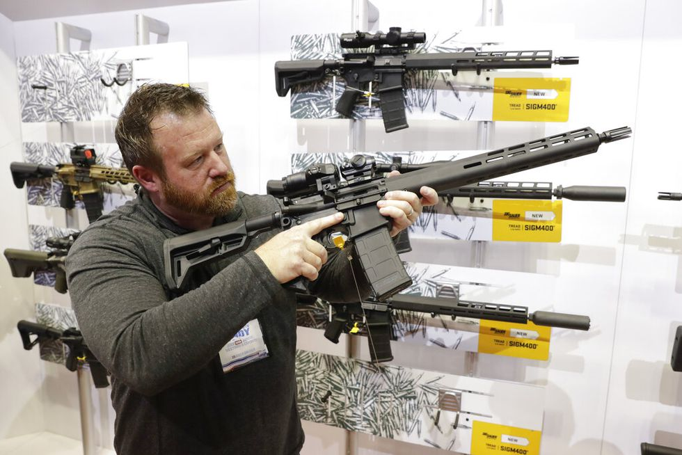 Bryan Oberc, Munster, Ind., tries out an AR-15 from Sig Sauer in the exhibition hall at the...
