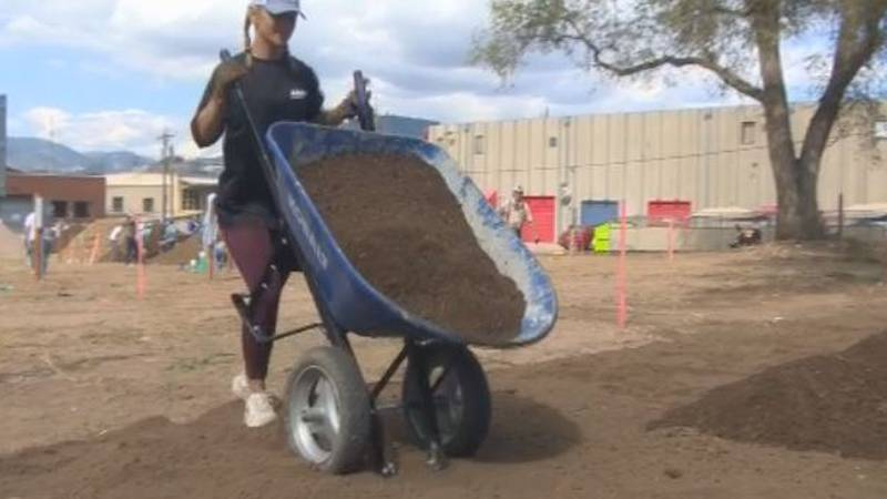 A volunteer dumps dirt at a site for those affected homelessness to have dignified housing in...