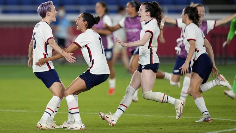 United States' Megan Rapinoe, left, celebrates with teammates after scoring the winning goal...