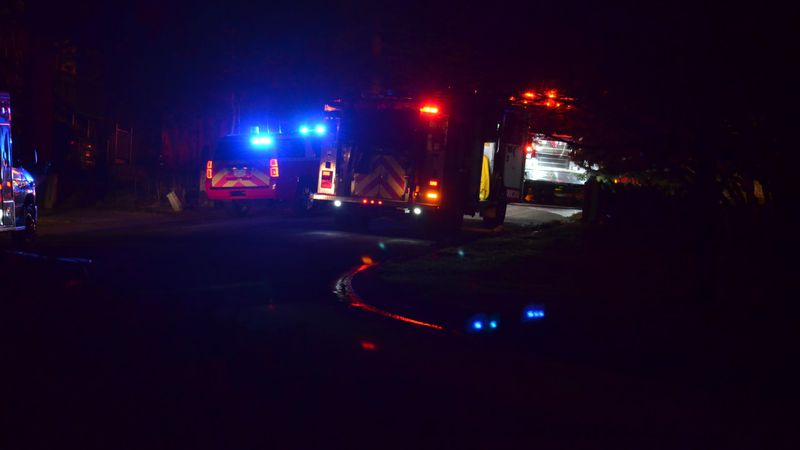 Fire trucks can be seen on a dark street in the Woodmen Valley area of Colorado Springs on...