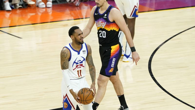 Denver Nuggets guard Monte Morris (11) reacts after turning the ball over as Phoenix Suns...