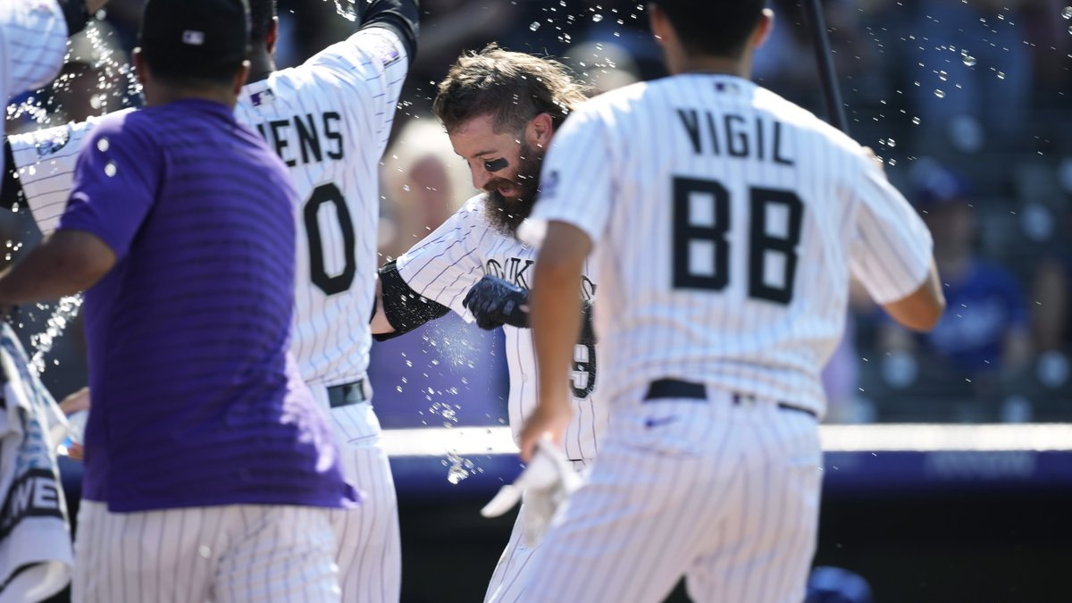 Colorado Rockies' Charlie Blackmon, center, is showered by teammates as Blackmon crosses home...