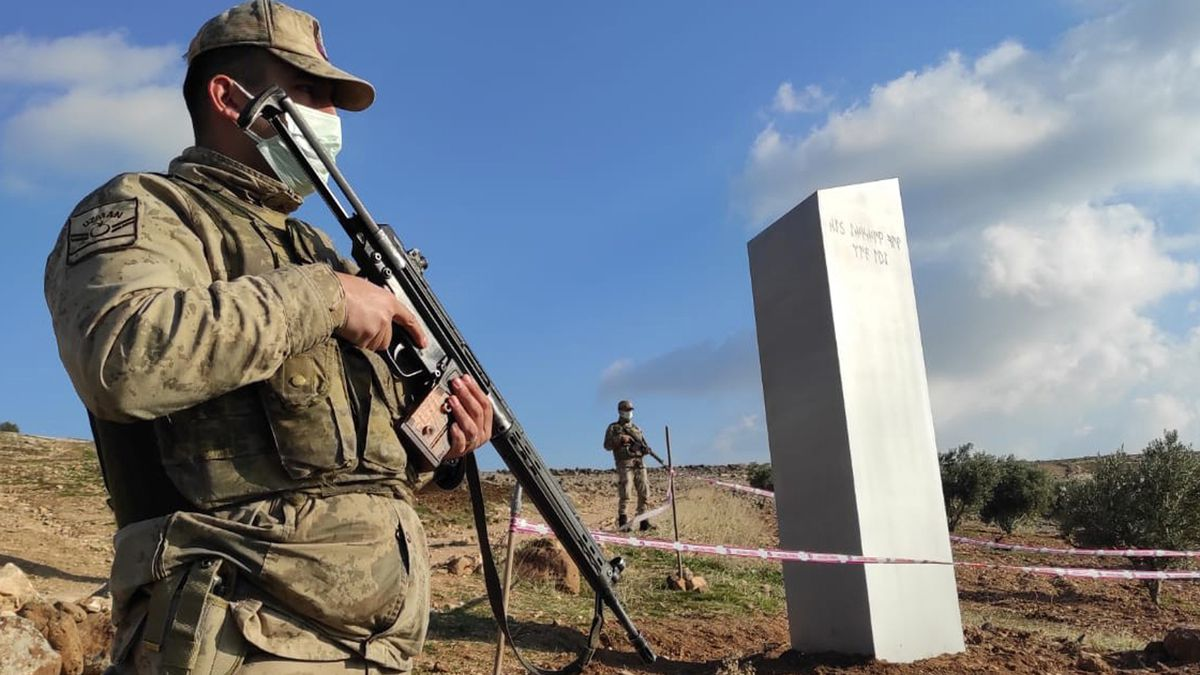 Turkish police officers guard a monolith, found on an open field near Sanliurfa, southeastern...