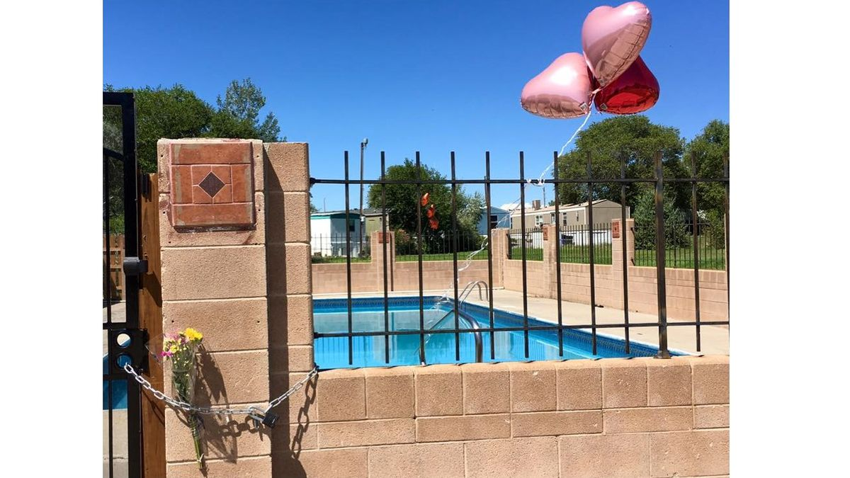 Mourners have left balloons and flowers tied to the swimming pool fence at Pueblo Grande Village, where three girls drowned Aug. 8.