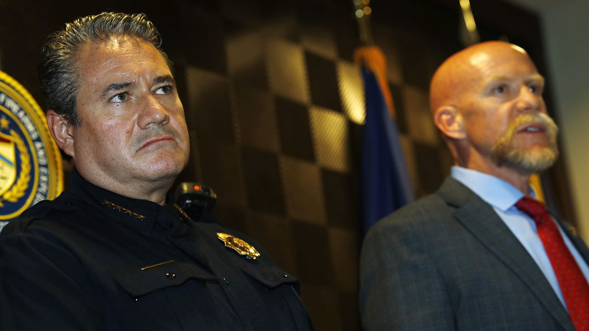 As David Booth, special agent in charge of the Bureau of Alcohol, Tobacco, Firearms and Explosives in the Rocky Mountain region, back, makes a point, Denver Police Chief Paul M. Pazen listens to the response during a news conference to announce that a dozen people have been arrested in several raids in the area as part of an unspecified operation Thursday, Nov. 7, 2019, in Denver. (AP Photo/David Zalubowski)