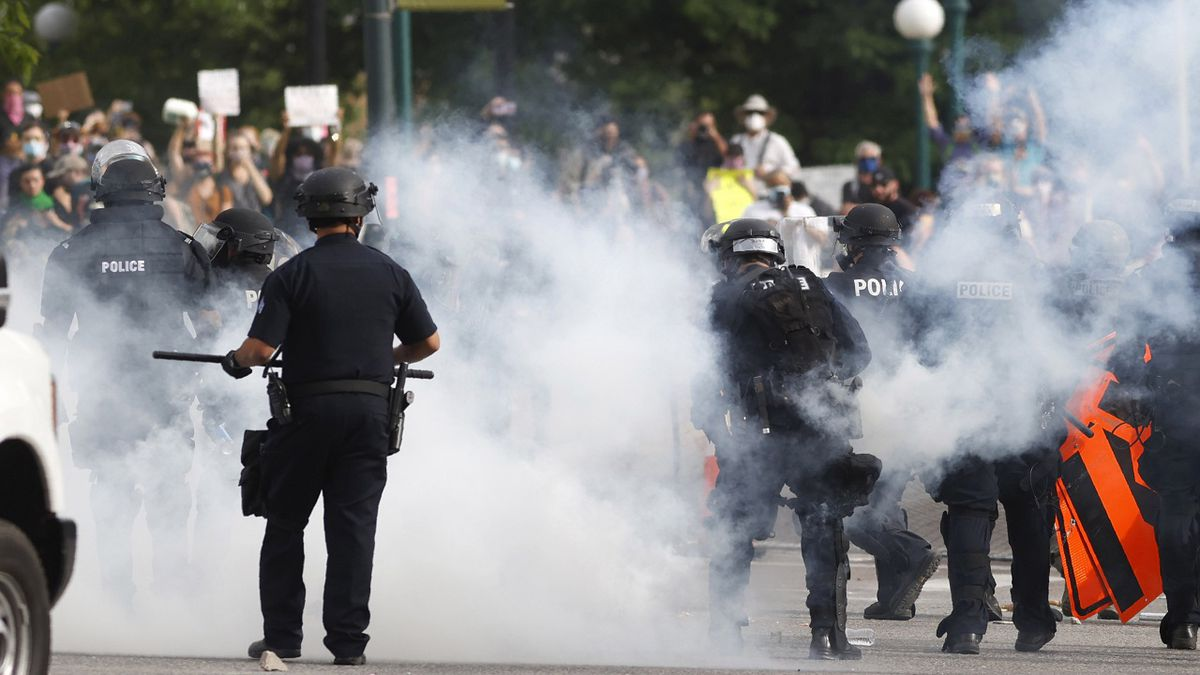Denver Police dodge their own tear gas canisters thrown back by participants during a protest...
