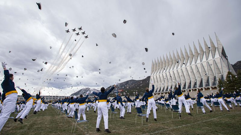 The class of 2020 toss their caps into the air as the Thunderbirds fly over Saturday, April...