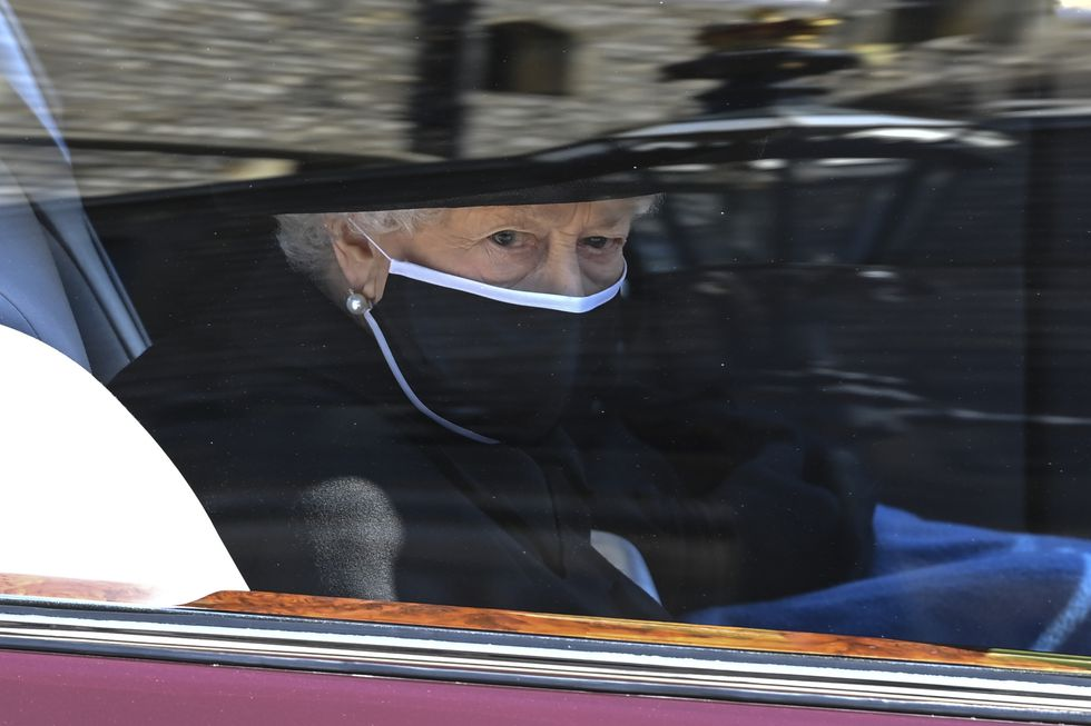 Britain's Queen Elizabeth II follows the coffin in a car as it makes its way past the Round...