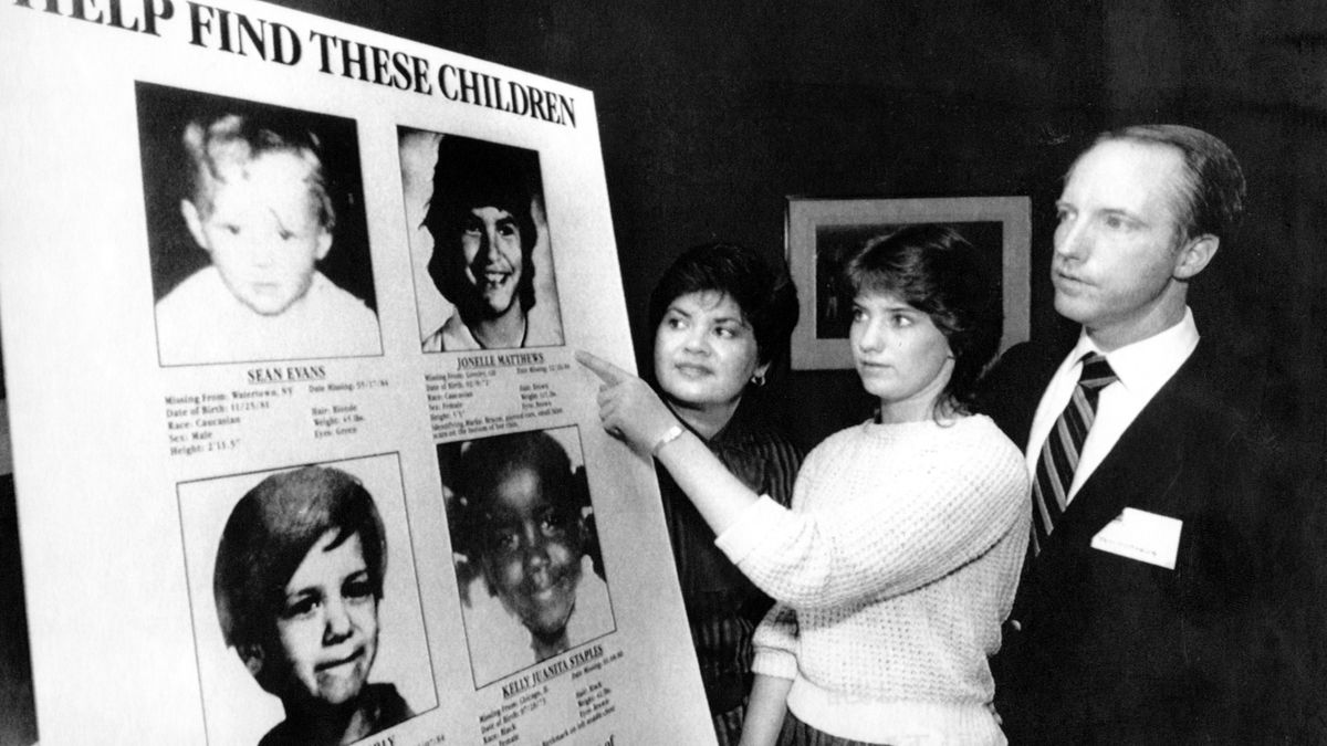 Jennifer Matthews, 16, points to a photo of her missing sister, Jonelle, 13, as parents Gloria and Jim Matthews, of Boulder, Colo., look on Friday April 19, 1985, in New York. Playhouse Video announced a poster program as part of a campaign to help locate missing children that it hopes will involve 24,000 nationwide video retail outlets and be seen by 144 million customers. (AP Photo/Ed Bailey)