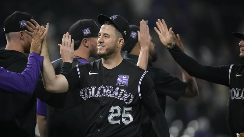 Colorado Rockies first baseman C.J. Cron is congratulated by teammates the team's 7-4 win in a...