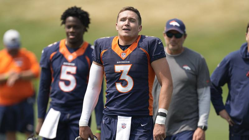 Denver Broncos quarterback Drew Lock, front, heads off the practice field with, from back left,...