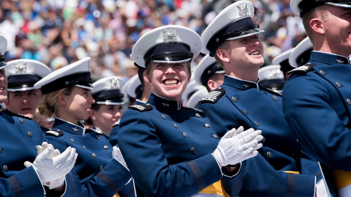 Cadets clap and smile as one of their classmates is invited to the stage to greet Donald J....