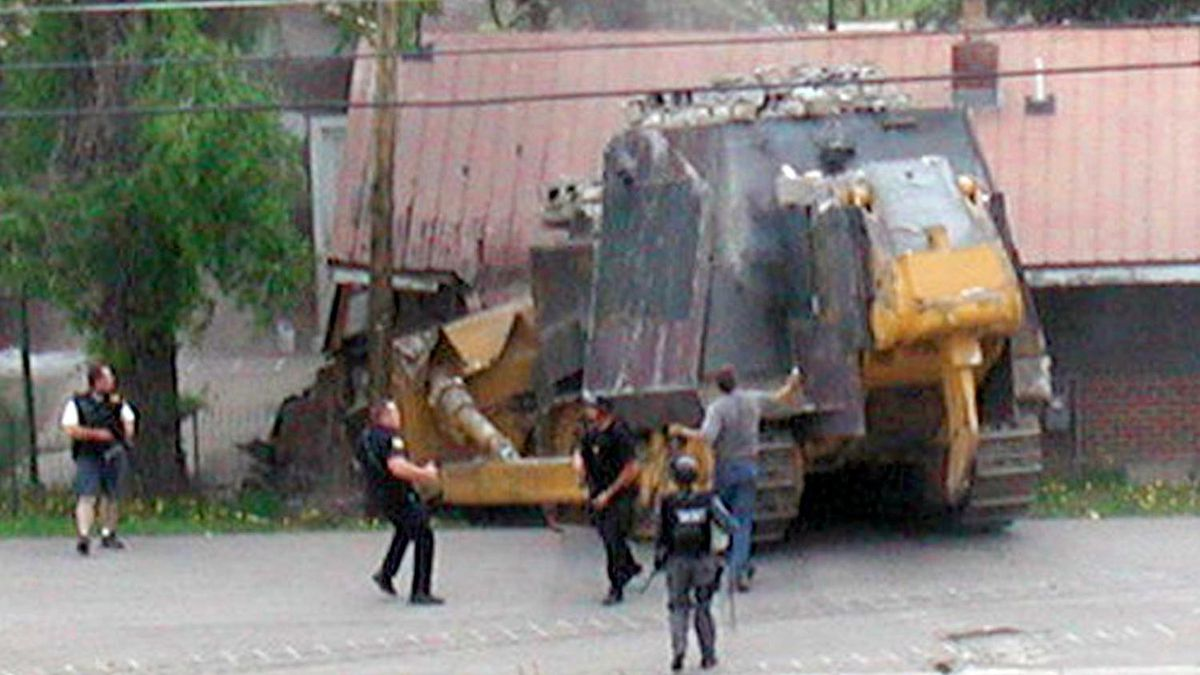 Police officers pursue fortified bulldozer driven by Marvin Heemeyer as it crashes into home, Granby, Colorado, photo courtesy AP.