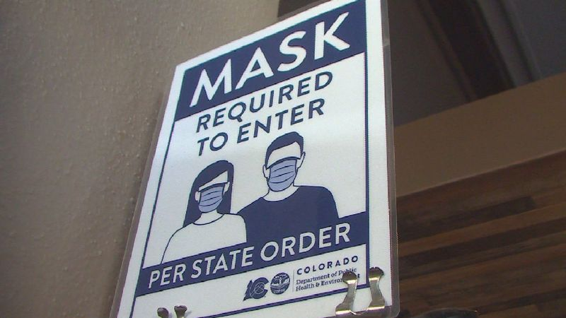 A Mask Required sign hangs up in the front of a Colorado Springs business.