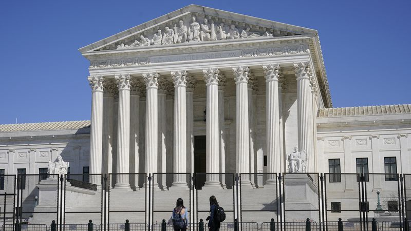 People view the Supreme Court building from behind security fencing on Capitol Hill in...