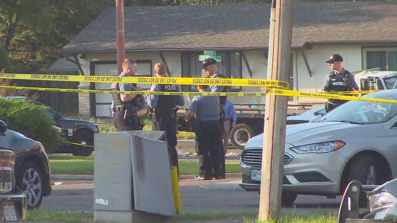 Police stand surrounded by crime tape immediately outside Woody's Bar and Grill off Pikes Peak...