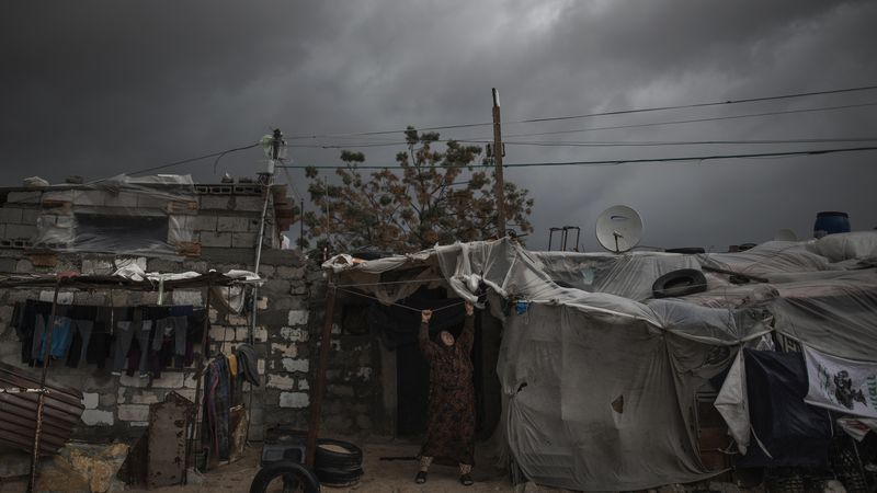A Palestinian woman checks the nylon cover on the roof of her house on a rainy day in a poor...