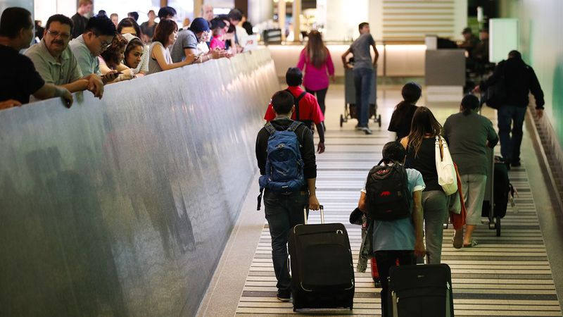 Travelers make their way up the arrival ramp at the Tom Bradley International Terminal at the...