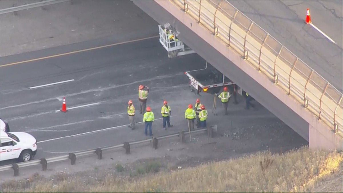 Road workers can be seen assessing a bridge at I-70 and Denver West Parkway on Sept. 23, 2021.