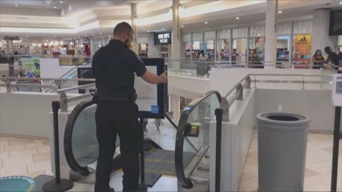 A police officer closes off an escalator where a 2-year-old child reportedly tumbled out of his...