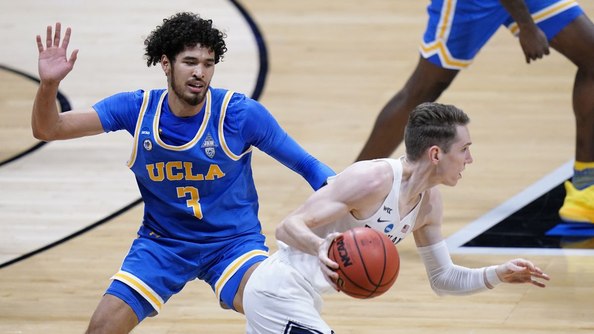 BYU guard Spencer Johnson (20) drives past UCLA guard Johnny Juzang (3) during the first half...