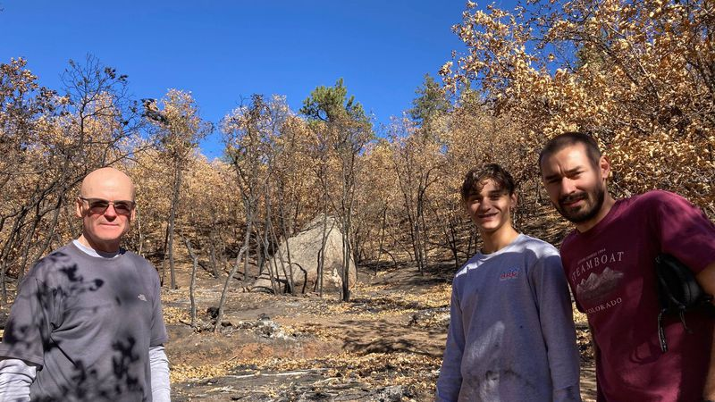 Some volunteers pose for a photo while they clean up the site of the Barr Trail Fire.