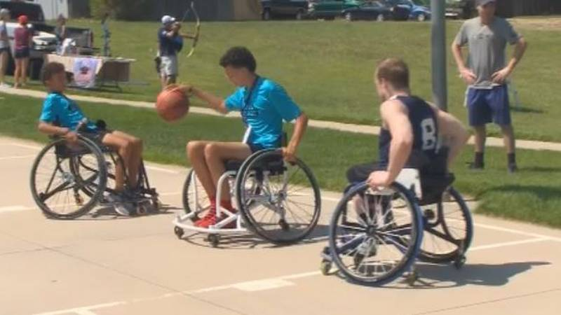 USA Wheelchair Basketball Olympic team member John Boie plays some hoops with some kids on...