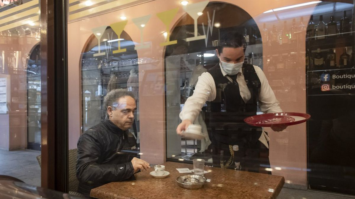 A waiter is serving a coffee to a guest at the restaurant Portico on the Piazza Grande in Locarno, Switzerland, Monday, May 11, 2020. Following the coronavirus lockdown, Switzerland reopens it's shops, fitness centers, restaurants and museums under strict restrictions for social distancing and hygiene measures today. (Ti-Press/Pablo Gianinazzi/Keystone via AP)
