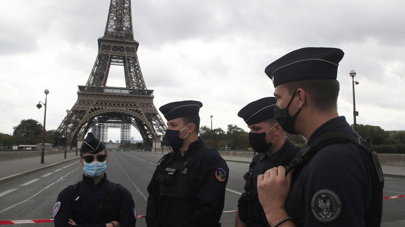 French police officers wear masks near the Eiffel Tower.
