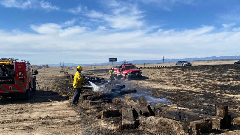 A firefighter extinguishing a hot spot at a fire along Highway 50 on March 7, 2021.