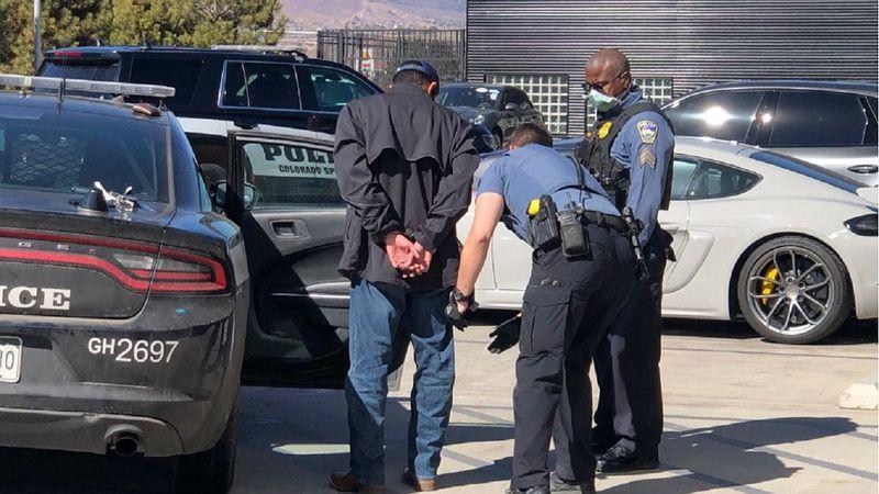 Police take a man into custody at a Colorado Springs Porsche dealership.