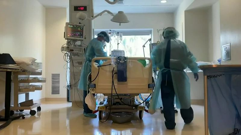 Doctors in a hospital room near a bed.