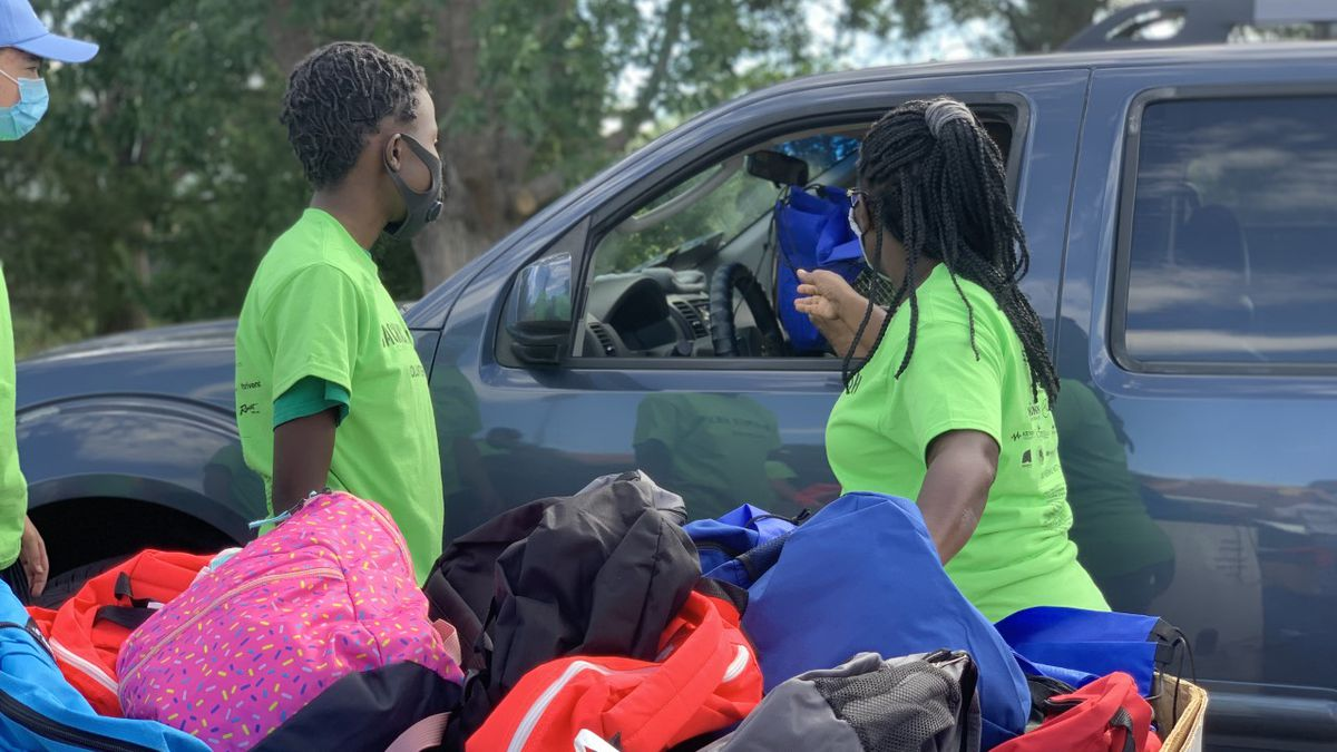 Two volunteers hand out backpacks and other school supplies at the Backpack Bash event on Saturday.