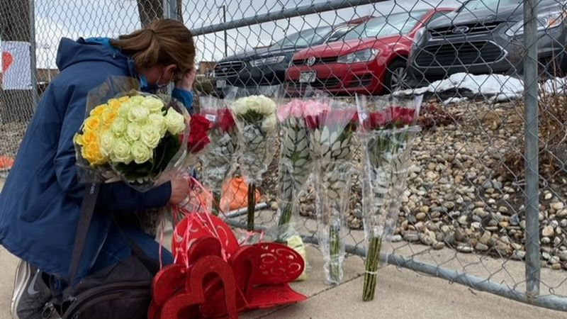 A woman leaves items at a memorial for the victims in the Boulder King Soopers shooting.
