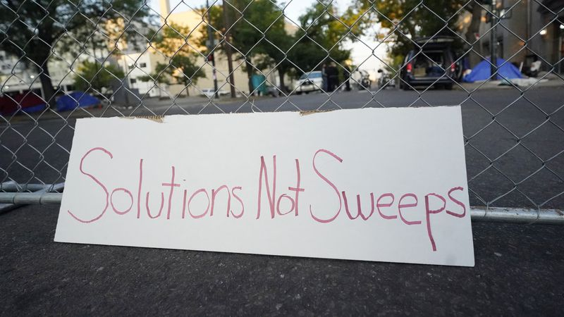 A sign leans against a cyclone fence surrounding a homeless encampment during a sweep around...