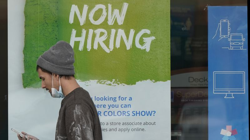 "A man walks past a ""Now Hiring"" sign on a window at a Sherwin-Williams store, Friday, Feb. 26,..."