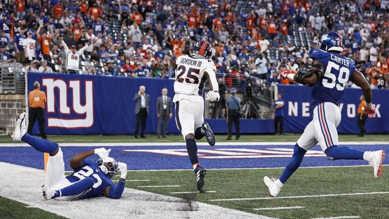 Denver Broncos running back Melvin Gordon (25) runs past New York Giants' Adoree' Jackson (22)...