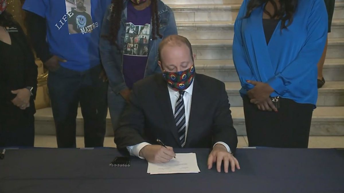 Gov. Jared Polis signs a sweeping police reform bill into law at the State Capitol on Friday, June 19, 2020.