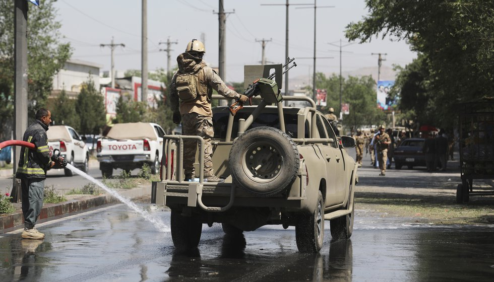 In this June 6, 2021 photo, Afghan security personnel leave the scene of a roadside bomb...