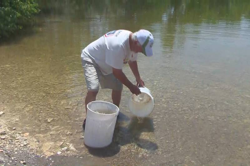 A man collects water from a lake near Colorado City as the area deals with a water shortage.