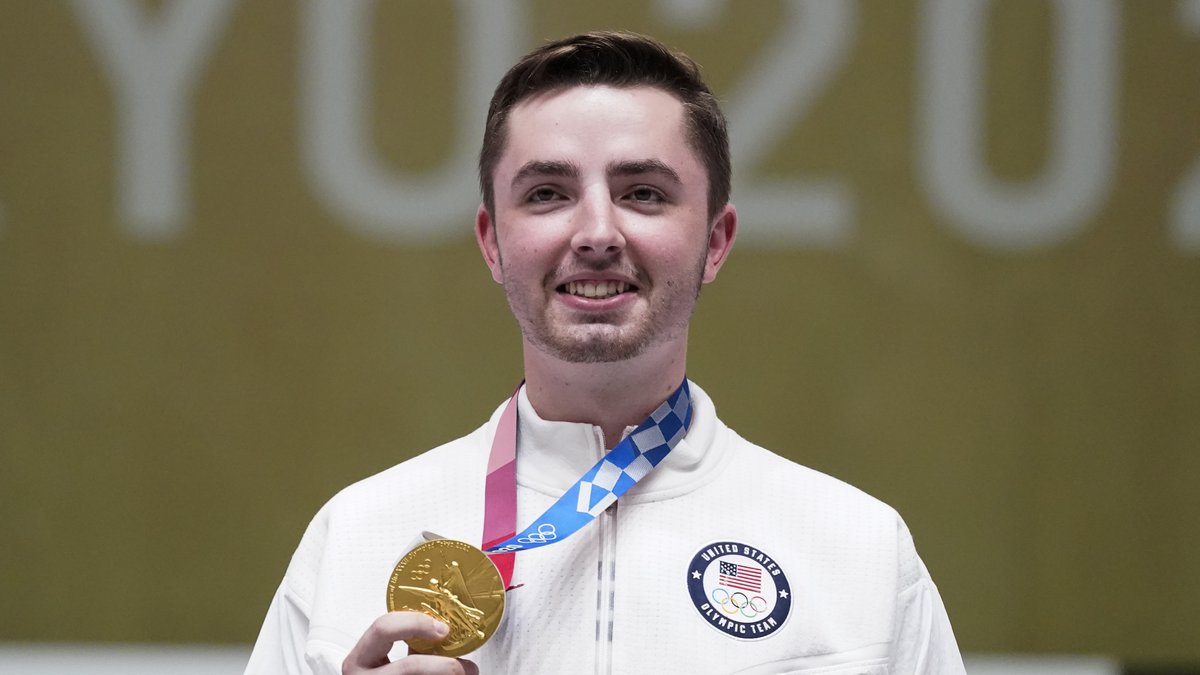 William Shaner, of the United States, holds his gold medal on after the men's 10-meter air...