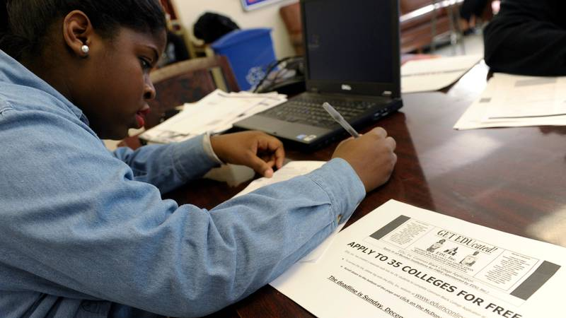 Akira Lee, a senior at Roosevelt High School, fills out a college enrollment application at her...