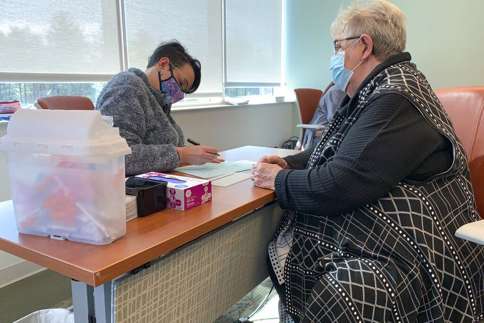 In this Thursday, Jan. 28, 2021 photo, A nurse asks 72-year-old Joyce Dugan a series of...