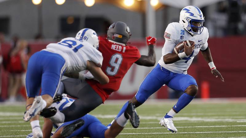 Air Force quarterback Haaziq Daniels, right, runs for yardage during the second half of an NCAA...